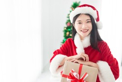 attractive asian female in santa claus costume, she holding gift box with hand in celebration seasonal, she feeling happy and smile, happy new years and Christmas celebration