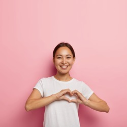Attractive Asian female makes heart shape gesture, expresses love, says be my valentine, smiles positively, wears white outfit, poses against pink wall with empty space. Body language concept