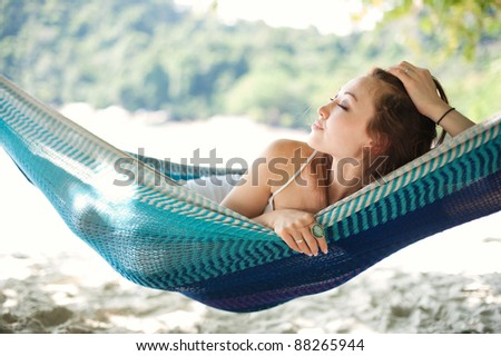 Attractive asian female relaxing on a hammock