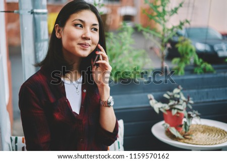 Attractive asian female teenager with cute smile on face making international conversation via advanced mobile phone while connected to 4g internet in roaming and spending free time outdoors