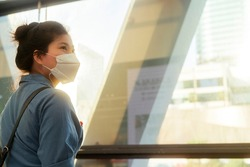 attractive asian female woman casual cloth wearing face mask protection standing next to big glasses modern frame window with sun light flare subset moment new normal lifestyle healthcare concept