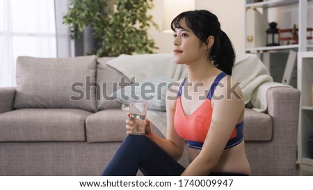 attractive asian girl in exercise outfit gulps down water and heaves a sigh of satisfaction. sportive chinese lady catches her breath and mops the sweat from her brow after workout.