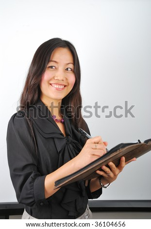 Attractive Asian girl writing in her notepad and smiling