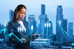 Attractive Asian HR director at international company is looking into personal organizer to plan business meeting to recruit highly qualified specialists. Social media icons over Singapore.