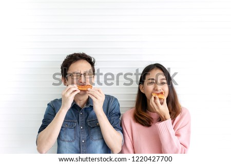 Attractive asian hungry couple eating pizza or fast food with smile and tasty facial expression on face with white wall background. Millennial lifestyle with friends concept. Man and woman enjoy meal.