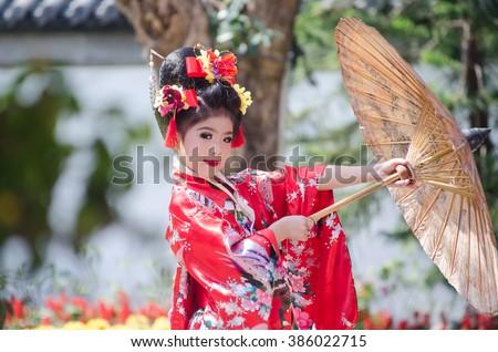 attractive asian little girl wearing traditional Japanese Kimono #386022715
