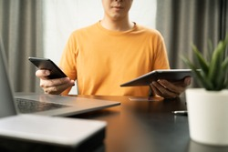 Attractive Asian man working with Multiple electronic device using internet connection with his partners on smartphone, Tablet and laptop Multitasking concepts.