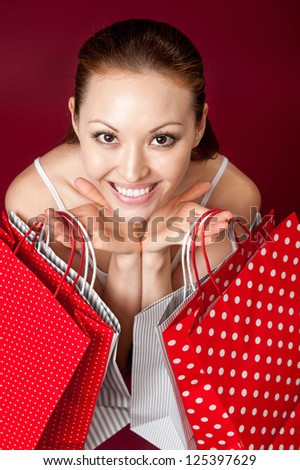 Attractive Asian Mixed Woman holding shopping bags looking up close up