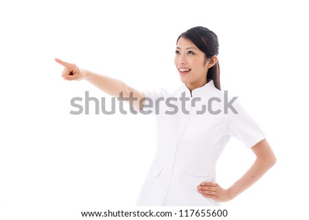attractive asian nurse pointing on white background