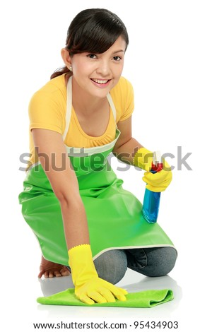attractive asian woman cleaning the floor while kneeling at home