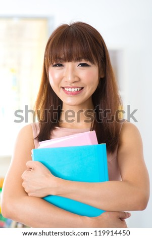 Attractive asian woman holding books at home