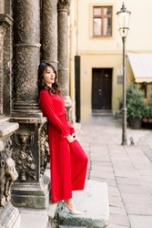 attractive asian woman in long red dress posing standing near the old building column in old city, love story or wedding image in europe