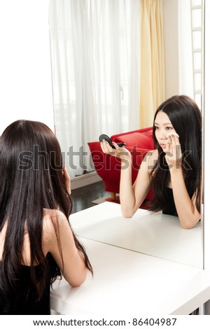 attractive asian woman making up front of mirror