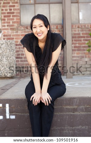 Attractive Asian woman outdoors wearing short sleeved black shirt and black pants