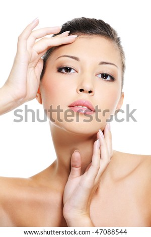 Attractive asian woman pampering her  face by beauty slender fingers - stock photo