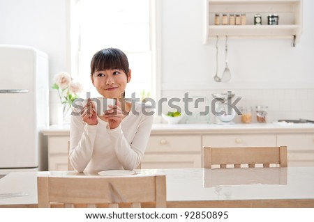 attractive asian woman relaxing in the kitchen
