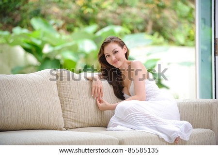 Attractive Asian woman sitting on a sofa in the living room