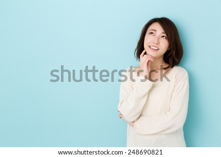 attractive asian woman thinking isolated on blue background