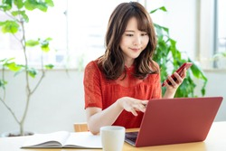 Attractive asian woman using a laptop PC and a smart phone.