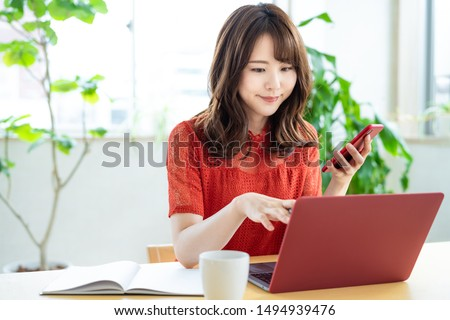 Photo of Attractive asian woman using a laptop PC and a smart phone.