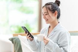 attractive asian woman using smart phone at morning