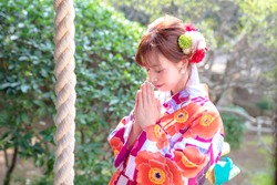 Attractive asian woman wearing japanese kimono praying at a Shinto shrine.