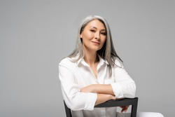attractive asian woman with grey hair sitting on chair isolated on grey
