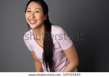 Attractive Asian woman with long black hair shot against a studio background.