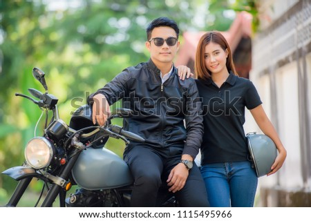 Attractive asian young sexy biker man put on sunglasses and girl in black jacket and helmet is looking and smiling while sitting on a motorcycle. #1115495966