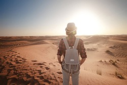 attractive asian young woman in plaid shirt in desert, treveling in UAE on safari, wearing hat and backpack, exploring nature of sandy beauty