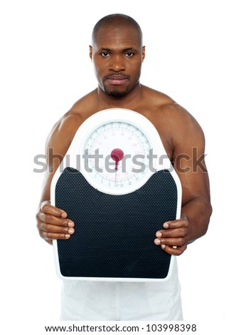 Attractive athlete showing weighing scale against white background