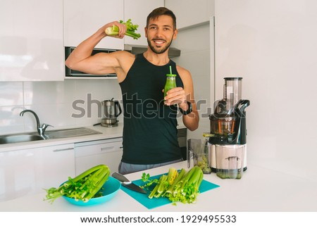 Attractive athletic active sportive man making fresh detox homemade celery juice in juicer machine at home in kitchen. Exercise and eating healthy. Detox diet for fitness. Healthy lifestyle.