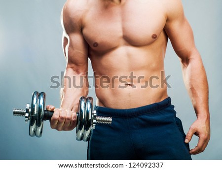 attractive athletic male torso with dumbbells