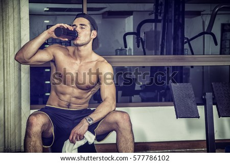 Attractive athletic shirtless young man drinking protein shake from blender in gym while looking at camera