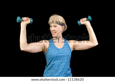 Attractive baby-boomer exercising with weights isolated over black