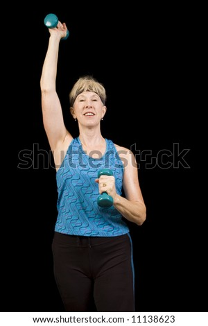Attractive baby-boomer woman exercising isolated 0ver black
