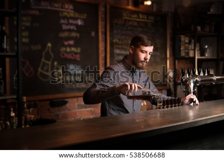 Attractive bartender is pouring a shots #538506688