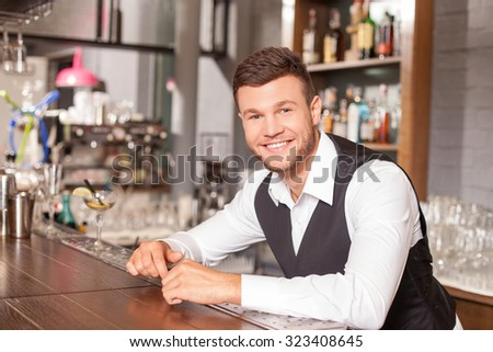 Attractive bartender is standing and leaning on counter is pub. He is looking forward with joy. The man is uniform is smiling