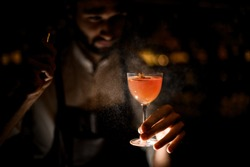 Attractive bartender serving a brown orange cocktail spraying on it in the dark on the bar counter