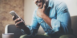 Attractive bearded African businessman using smartphone while sitting on sofa at his home.Concept of young people working mobile devices.Closeup with a selected focus.Blurred background.Wide