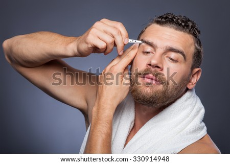 Attractive bearded guy is plucking eyebrows with concentration. He is standing and holding pincers. The hipster is looking forward seriously. Isolated #330914948
