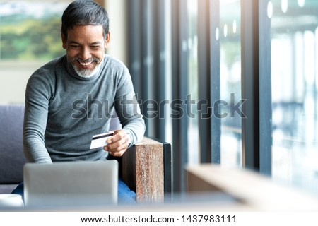 Attractive bearded hipster asian father or Hispanic old man using Laptop and credit card payment shopping online with customer network connection via omni channel system. Older man with technology.