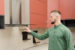 Attractive bearded man in a green shirt turns on a fume hood in a modern kitchen.