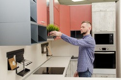 attractive bearded man puts a decorative pot with artificial grass on a fume hood in a modern kitchen.