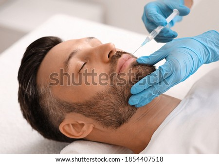 Attractive bearded man visiting aesthetic clinic, getting lips filler, closeup. Middle aged businessman having beauty injection at male spa salon. Face care, anti-aging treatment for men concept Foto stock ©