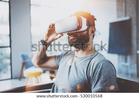 Attractive bearded man wearing virtual reality glasses in modern interior coworking studio.Hipster using smartphone with VR goggles headset.Horizontal,film effect,flare, blurred background