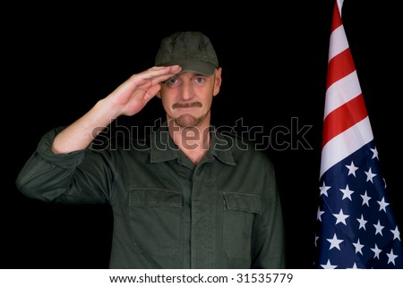 Attractive bearded middle aged man, soldier,  saluting American flag, studio shot, black background.