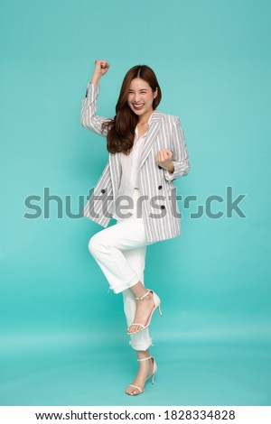 Attractive beautiful Asian woman standing and hands up raised arms from happiness, Excited businesswoman winner success concept