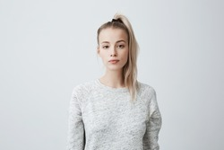 Attractive beautiful female with blonde pony tail, feeling self-assuarance while posing against blank studio wall. Confident woman with dark eyes dressed casually isolated against gray background