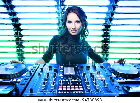Attractive beautiful girl DJ in the nightclub